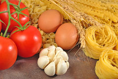 Uncooked Italian pasta, ripe tomatoes branch, garlic and eggs Royalty Free Stock Photos