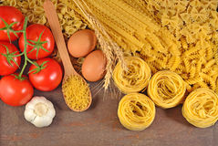 Uncooked Italian pasta, ripe tomatoes branch, garlic and eggs Stock Photography