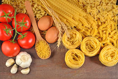 Uncooked Italian pasta, ripe tomatoes branch, garlic and eggs Royalty Free Stock Image