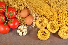 Uncooked Italian pasta, ripe tomatoes branch, garlic and eggs Stock Images