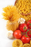 Uncooked Italian pasta, ripe tomatoes branch and garlic on a whi Stock Photography