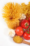 Uncooked Italian pasta, ripe tomatoes branch and garlic on a whi Royalty Free Stock Photo