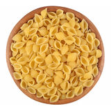 Uncooked italian pasta shells in a wooden bowl on a white Stock Images
