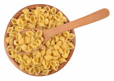 Uncooked italian pasta shells in a wooden bowl on a white Royalty Free Stock Images