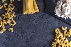 Uncooked italian pasta spaghetti and cavatappi with flour from durum wheat. Concept of The composition of food design. Uncooked italian pasta spaghetti and stock photography