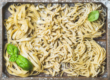 Uncooked Italian pasta in wooden tray with basil and flour Royalty Free Stock Photo