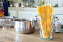 Uncooked Italian row of spaghetti in glass jars  on wooden table Royalty Free Stock Photos