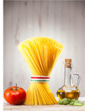 Uncooked Italian spaghetti , oil, herbs and tomato Royalty Free Stock Photo