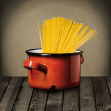 Uncooked Italian spaghetti in a red pot. Uncooked Italian spaghetti in a colorful red enameled pot standing on a rustic wooden kitchen counter while preparing a Royalty Free Stock Photo