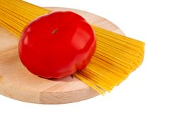 Uncooked italian spaghetti with tomato. Royalty Free Stock Photo