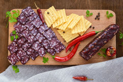 Uncooked jerked sausage, cheese, cutting slices on a cutting board Royalty Free Stock Images