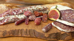 Uncooked jerked sausages, baguette and figs. Camera movement near uncooked jerked sausages, baguette and figs on a wooden board stock footage
