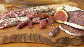 Uncooked jerked sausages, baguette and figs. Circular movement of the camera around uncooked jerked sausages, baguette and figs on a wooden board stock video