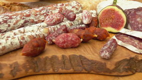 Uncooked jerked sausages. Jerked sausages, baguette and figs on a wooden board stock footage