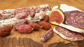 Uncooked jerked sausages. Jerked sausages and figs on a wooden board stock video footage