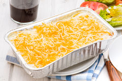 Uncooked lasagna in aluminum tray on wooden. Table stock images