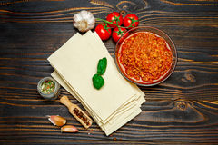 Uncooked lasagna pasta sheets and bolognese sauce Royalty Free Stock Images