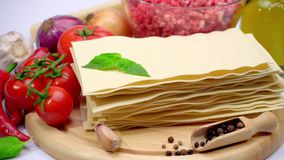 Uncooked lasagna pasta sheets and vegetables. Dried uncooked lasagna pasta sheets and vegetables stock video