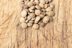 Uncooked lentils over wooden table close up. Traditional spanish ingredient Stock Image