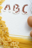 Uncooked macaroni and eggs on wheat flour Stock Photography