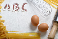 Uncooked macaroni, whisk and eggs Royalty Free Stock Photography