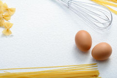 Uncooked macaroni, whisk and eggs on wheat flour Royalty Free Stock Photos