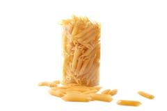 Uncooked makaron na białym tle, Makaron w przejrzystym szkle Typowy Włoski karmowy makaron w szkle obraz royalty free