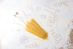 Uncooked makaronu spaghetti włoch i makaron zaznaczamy na floured białym tle Karmowej podróży kuchni włoski pojęcie obrazy stock