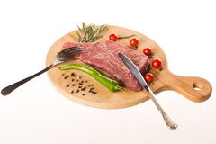 Uncooked meat steak on wooden desk with rosemary, pepper, tomatoes, fork and knife royalty free stock photography