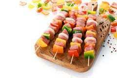Uncooked meat and vegetable kebabs. With colorful red, yellow and green sweet bell pepper, onion and tomato ready on a wooden board for grilling with fresh Royalty Free Stock Photos