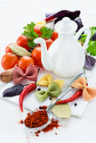 Uncooked multicolored pasta with tomatoes, fresh herbs and spice Stock Image