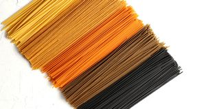 Uncooked multicolored spaghetti. Top view of bunches of uncooked spaghetti of different natural colored lying in row on white background stock photos