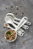 Uncooked multigrain rice in porcelain measuring spoons on wooden background Stock Photos