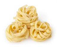 Uncooked nests of tagliatelle pasta isolated on white. Background with clipping path royalty free stock photography