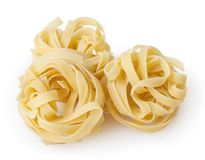 Uncooked nests of tagliatelle pasta isolated on white. Background with clipping path royalty free stock photo