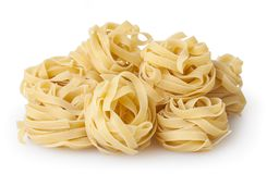 Uncooked nests of tagliatelle pasta isolated on white background. With clipping path stock images