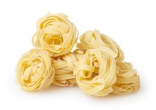 Uncooked nests of tagliatelle pasta isolated on white. Background with clipping path royalty free stock image