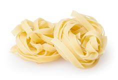 Uncooked nests of tagliatelle pasta isolated on white background. With clipping path royalty free stock photos