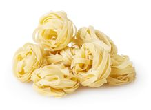 Uncooked nests of tagliatelle pasta on white background. With clipping path royalty free stock photography