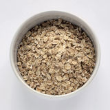 Uncooked oatmeal spilling from a bowl. On white background stock photography