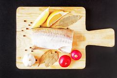 Uncooked ocean fish and fresh vegetables on rustic wooden cutting board over black backdrop. Top view.  Royalty Free Stock Photos