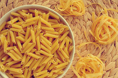Uncooked pasta. A bowl with uncooked penne rigate and some uncooked tagliatelle, with its characteristic nest shape Stock Image