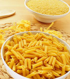 Uncooked pasta. A bowl with uncooked penne rigate, some uncooked tagliatelle with its characteristic nest shape, and a bowl with pastina in the background stock image