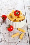 Uncooked pasta and cherry tomatoes in a bowl Royalty Free Stock Photography