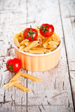 Uncooked pasta and cherry tomatoes in a bowl Stock Image