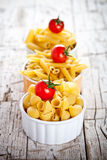 Uncooked pasta and cherry tomatoes in three bowls Royalty Free Stock Images