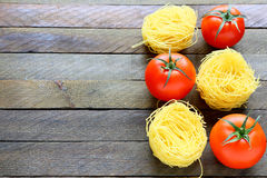 Uncooked pasta and fresh tomatoes royalty free stock photography