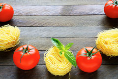 Uncooked pasta and fresh tomatoes Stock Photography