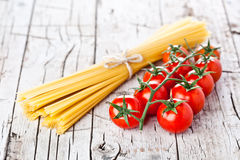 Uncooked pasta and fresh tomatoes Royalty Free Stock Photo