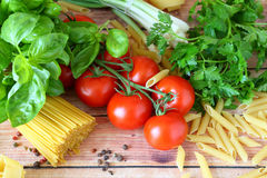 Uncooked pasta and fresh vegetables Stock Photos